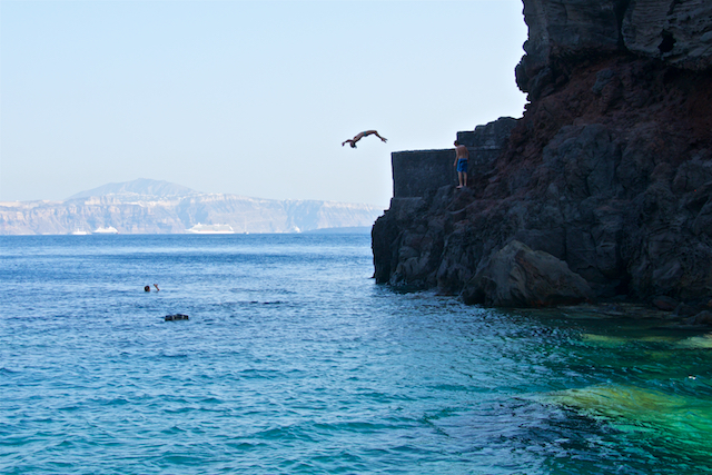 Jumping off rocks in Santorini